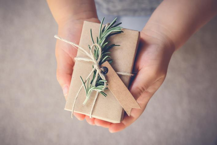 Holiday gift wrap in brown paper with a rosemary sprig attached