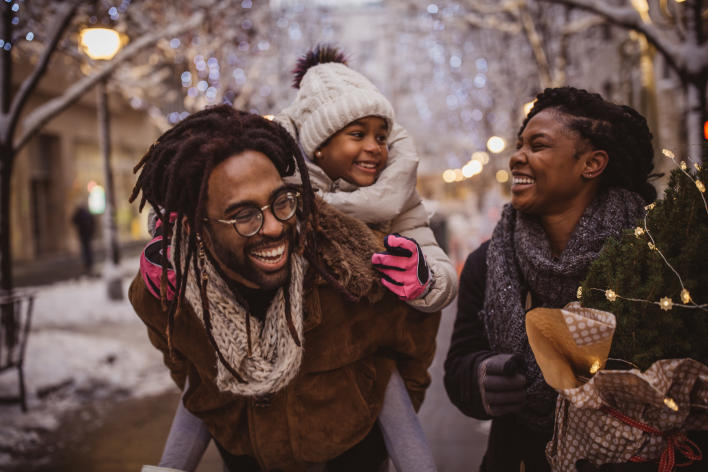 Black man carrying a child on his back with a woman beside them carrying a small christmas tree on snowy evening