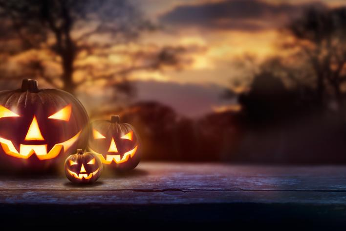 2 halloween pumpkins with a mountain range in the background