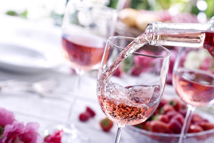 Rose' wine being poured into a wine glass on a pink and white table setting