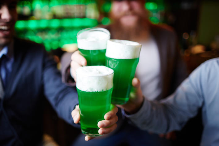 3 males holding up green beers