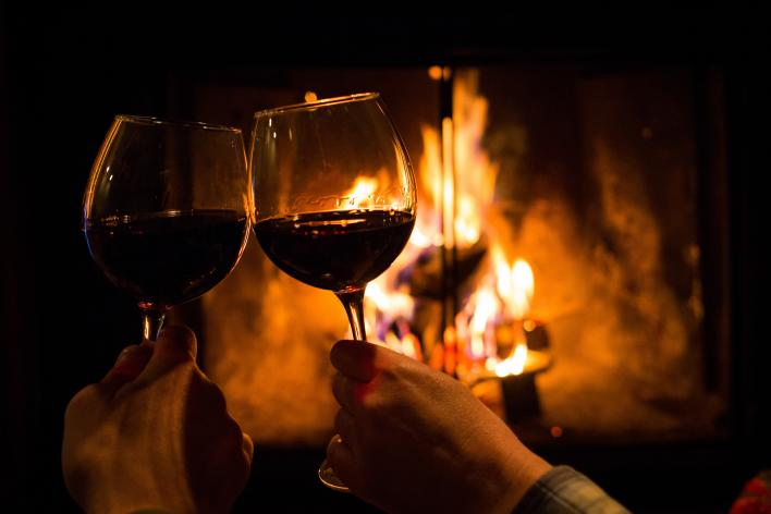Clinking wine glasses in front of fireplace