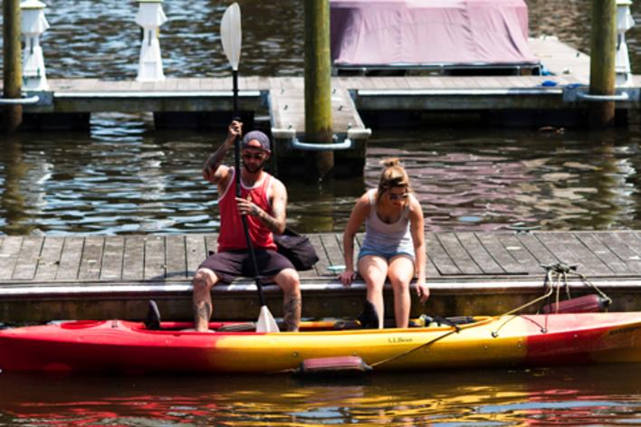 A man and a woman sitting on a boardwalk getting ready to get into a kayak