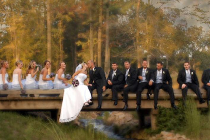 A wedding party sitting on a bridge