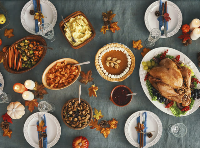 A table filled with Thanksgiving dishes like turkey and vegetables