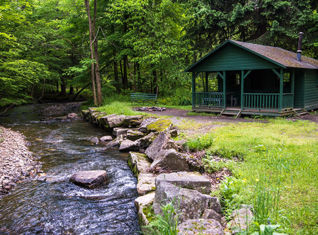 A photo of the exterior of a green cabin at Allegheny State Park