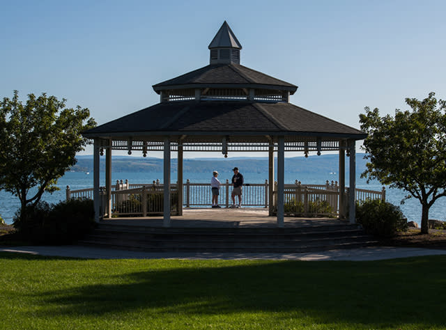 Two people standing in a gazebo overlooking Canandaigua Lake