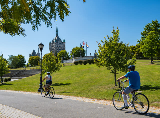 A photo of two people bicycling on the Empire Trail Corning Preserve