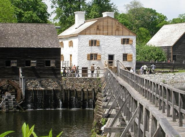The exterior of Phillipsburg Manor Mill and Bridge from across a bridge