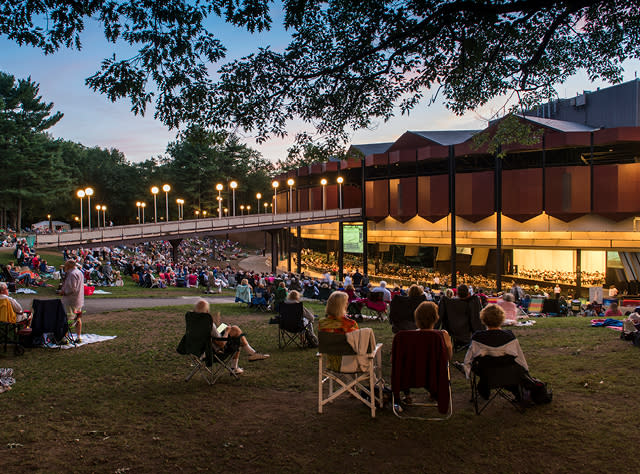 A photo of people sitting outside the Saratoga Performing Arts Center's Ampitheatre