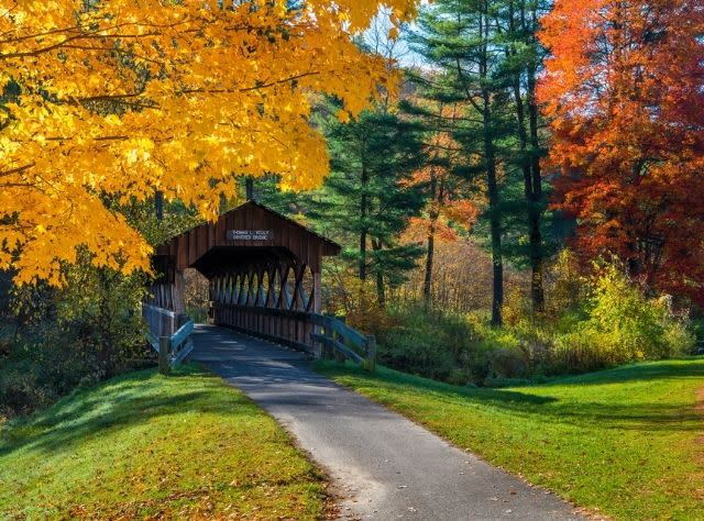 The Thomas L. Kelly Covered Bridge surrounded by fall foliage colors of yellow, green and orange