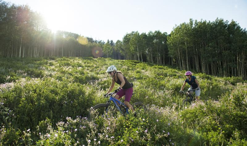 Two women mountain biking across a meadow with sunburst