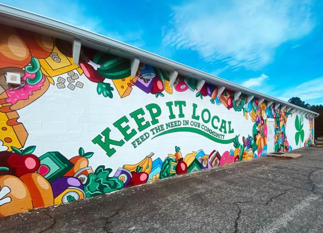 """Mural with fresh fruits and vegetables with """"keep it local feed the need in our community"""" written"""