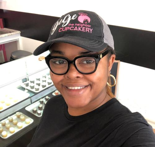 Woman in glasses and hat with gege cupcakery on the hat