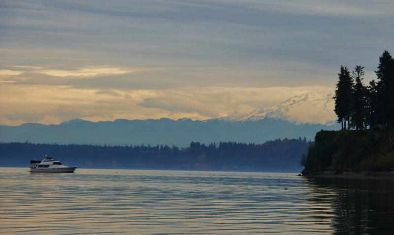 Mount Rainier peeks through the clouds overlooking the water at Tolmie State Park