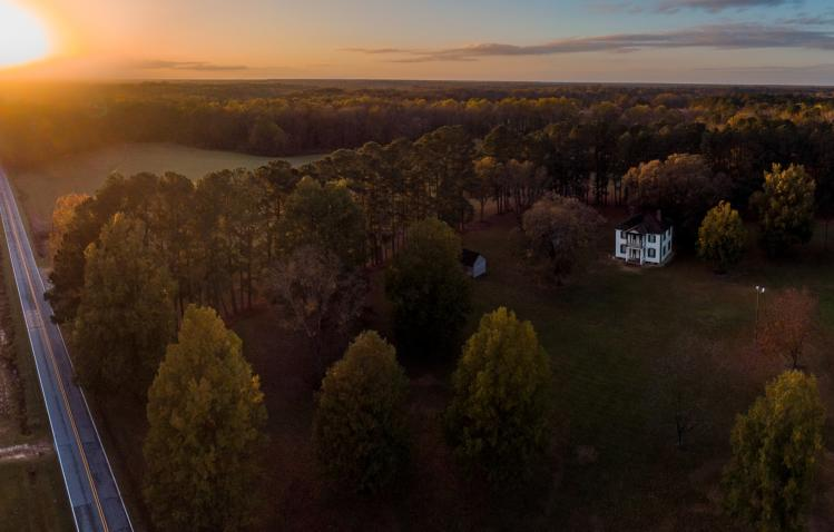 The sunsets in autumn over the fields and historic buildings of Bentonville Battlefield