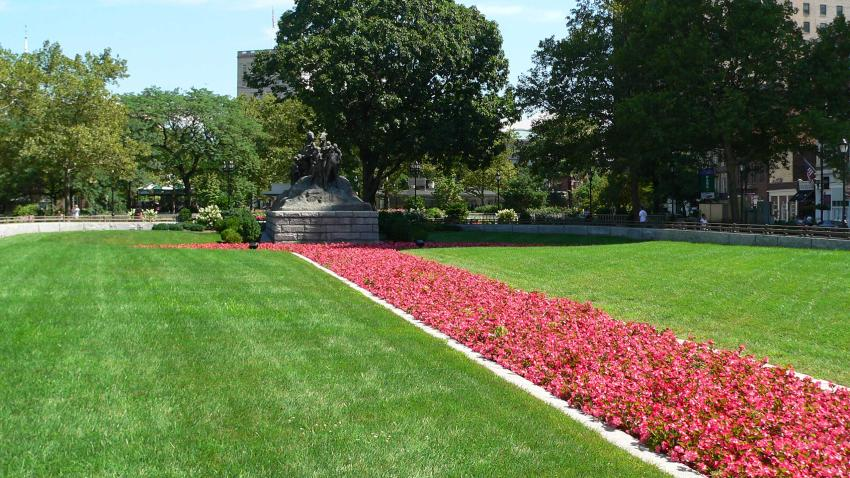 red flowers leading up to scupture in Military Park