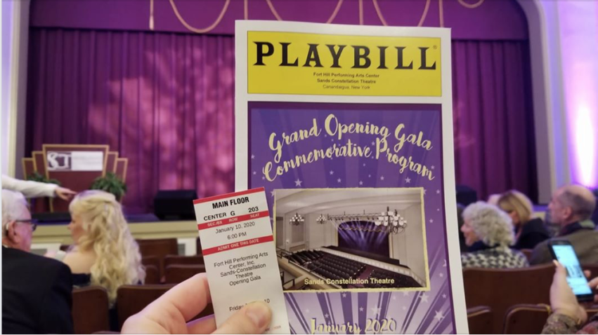 A hand holding a playbill and a ticket in front of the stage