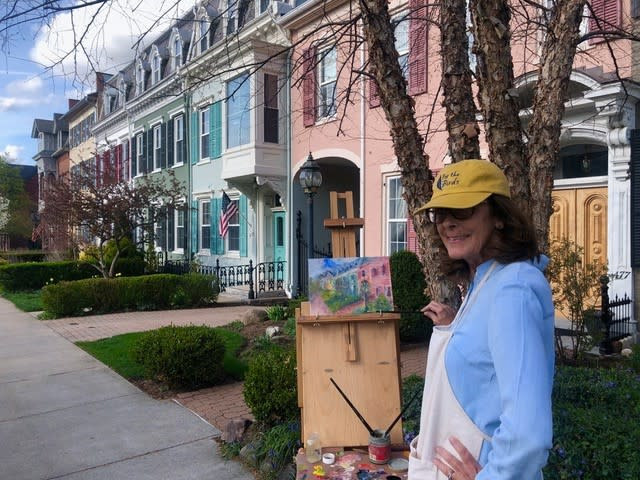 Woman painting color row houses on canvas easel