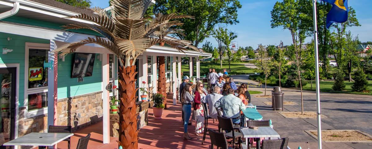 People dining on the outdoor patio at Somewhere Pub in River Prairie