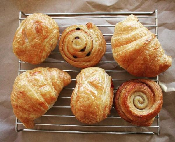 Six assorted croissants and rolls on a cooling rack from Mi-Sant Banh Mi