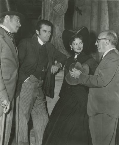 Melvyn Douglas, Gregory Peck, and Ava Gardner speaking with director Robert Siodmak on the set of The Great Sinner.