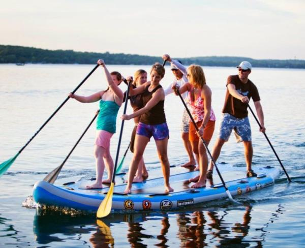 Group of girls on a large stand up paddle board