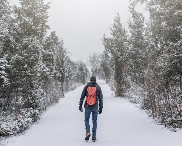 man walking on winter trail
