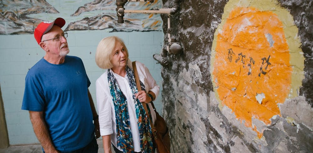 Eddie Beach and Sherry Edwards look at an original inscription by a Japanese POW at Pythian Castle in Springfield, Missouri