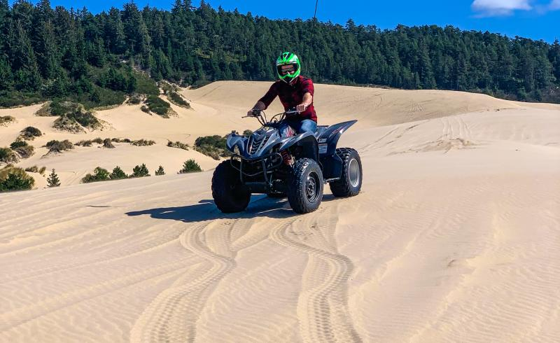 A man sits on an ATV on top of a large sand dune with forest in the background.
