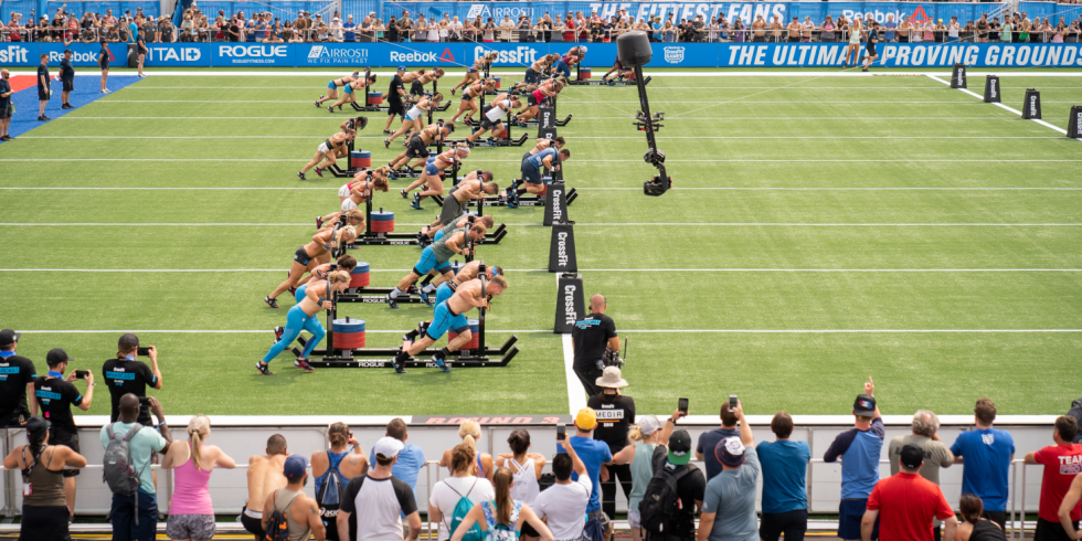 A group of competitor push sleds with weight on them across a field