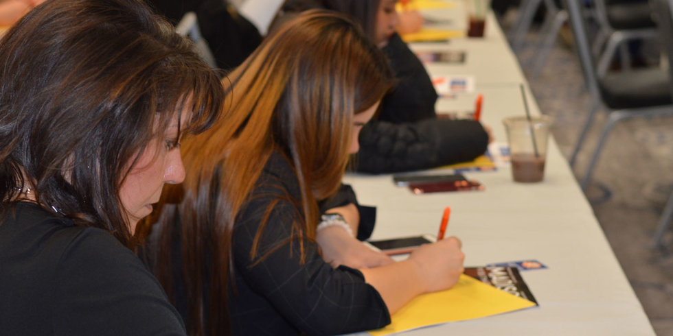 A woman jots down notes on a yellow sheet of paper during the March 2018 Industry Insider Training