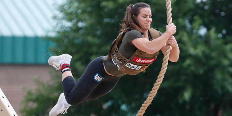 A woman swings on a rope while competing in the CrossFit Games