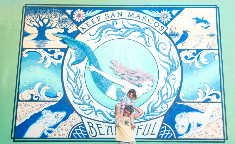 Father and daughter pose in front of a mural of a mermaid.