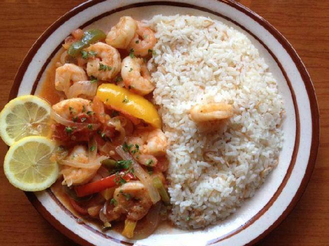 A plate of shrimp, rice, vegetables, and seasonings from Cedars Lebanese Restaurant