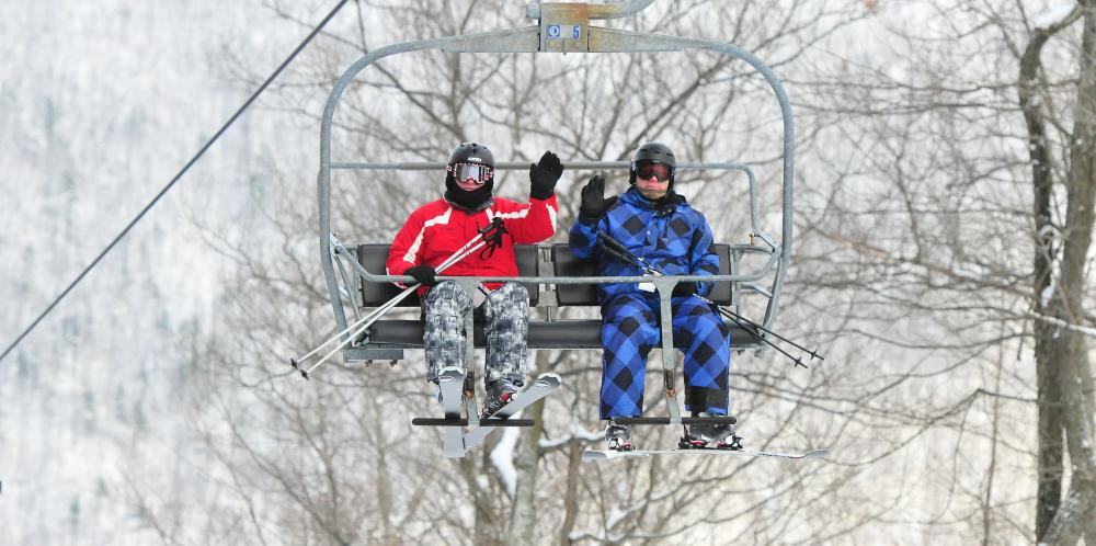 Two skiers at Bristol Mountain waiving on the lift