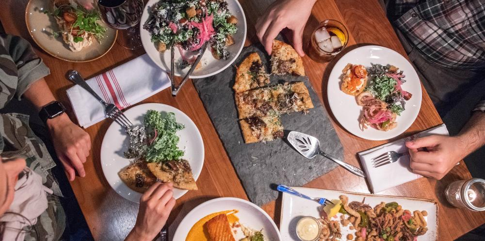Table of salad, pizza, and more being shared between two people