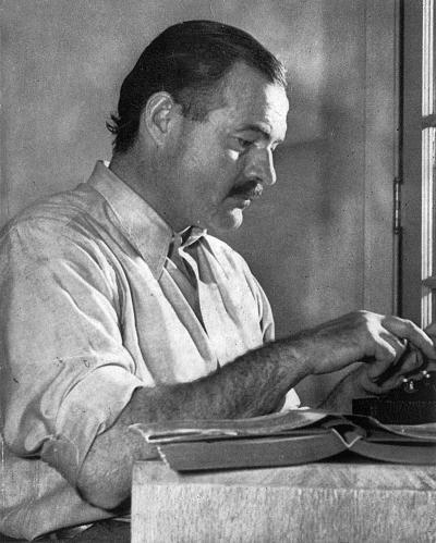 Ernest Hemingway sitting at a desk