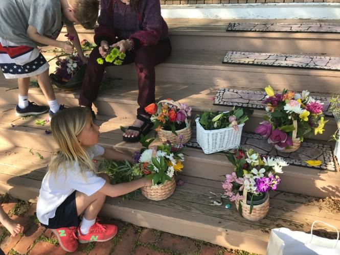 Kids creating their own May Day Baskets on their front porch stairs.