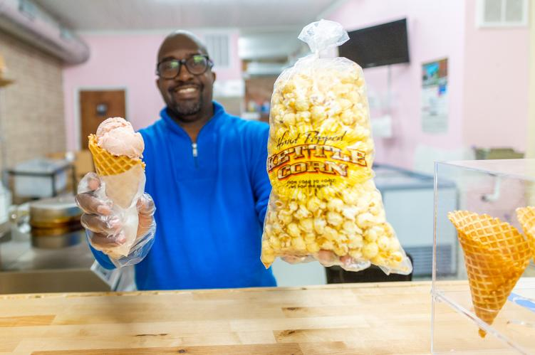 Man reaching over wooden counter holding an ice cream cone and bag of popcorn
