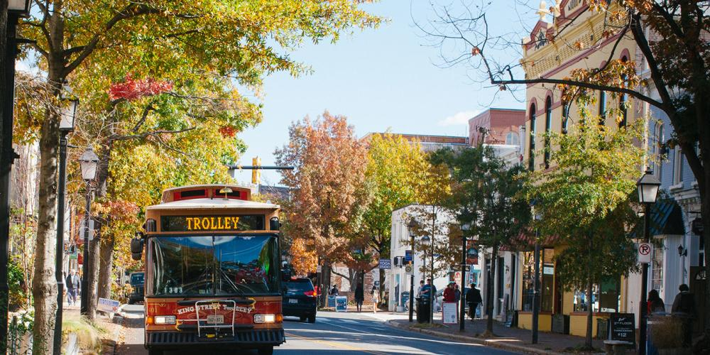 Trolley Going Down Street In Fall