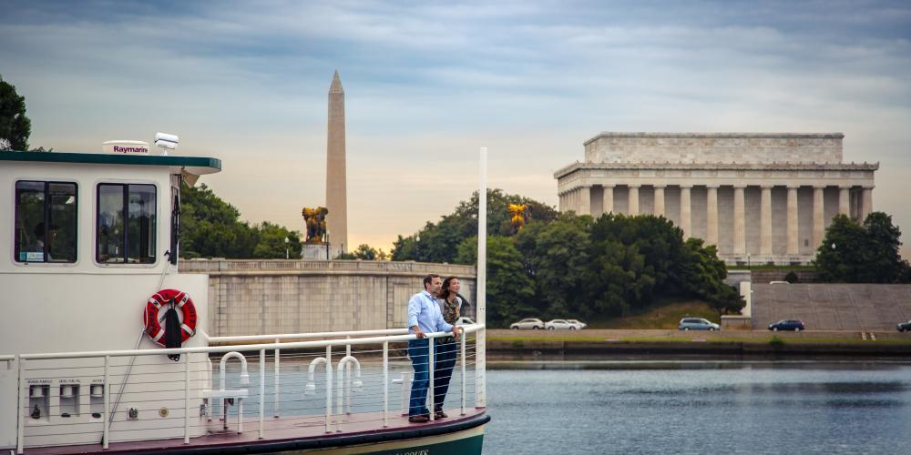A couple on a water taxi passing the Washington Monument and Lincoln Memorial