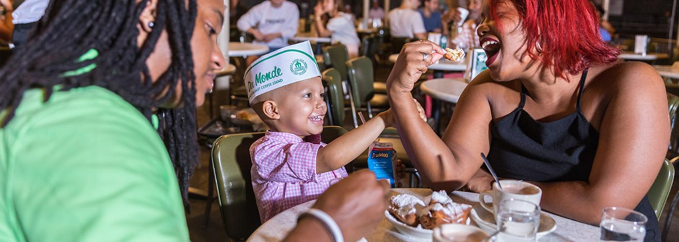 Family enjoying beignets at Cafe du Monde