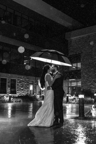 Outside the Marian H Rochelle Gateway Center Laramie Wyoming, wedding kiss umbrella in the rain