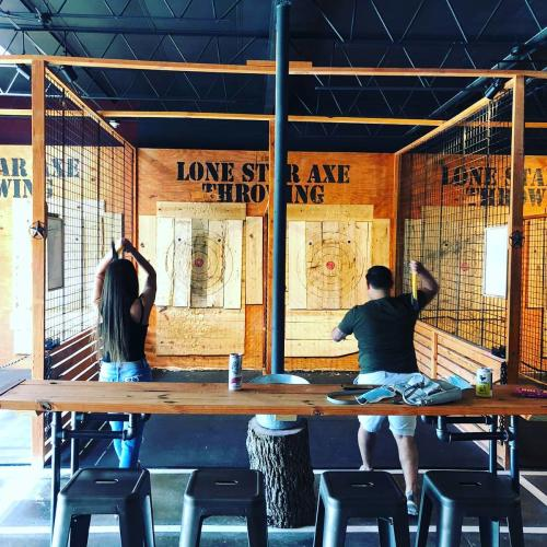 Two people throwing axes at Lone Star Axe Throwing