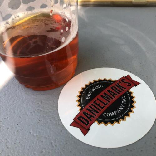 A partially consumed glass of beer sits next to the Danielmark's branded coaster in Cheyenne, Wyoming