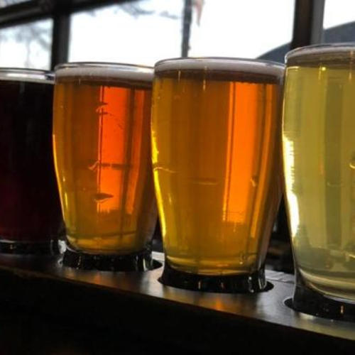 A flight of beers from Freedom's Edge Brewery in Cheyenne, Wyoming, backlit by the glass garage door