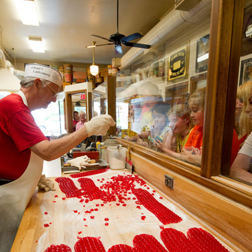 A candy maker cuts cinnamon red hot drops at Schimpff's Confectionary in Jeffersonville, IN