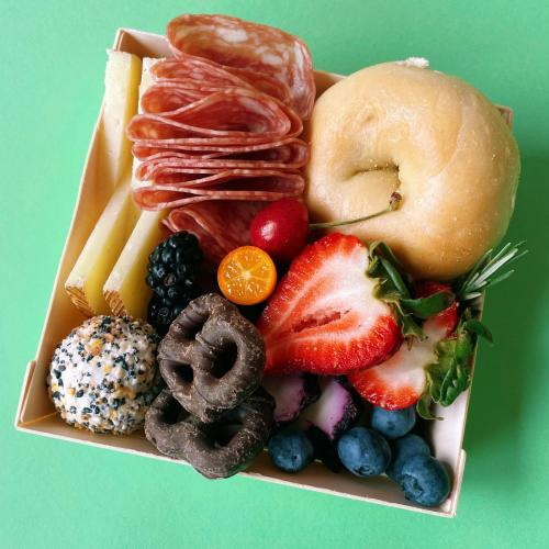 To-go container with a bagel, meats and cheese from Pride Bar Brunch