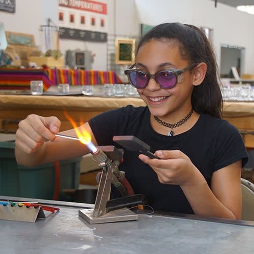 Girl blowing glass at Glass Axis in Franklinton